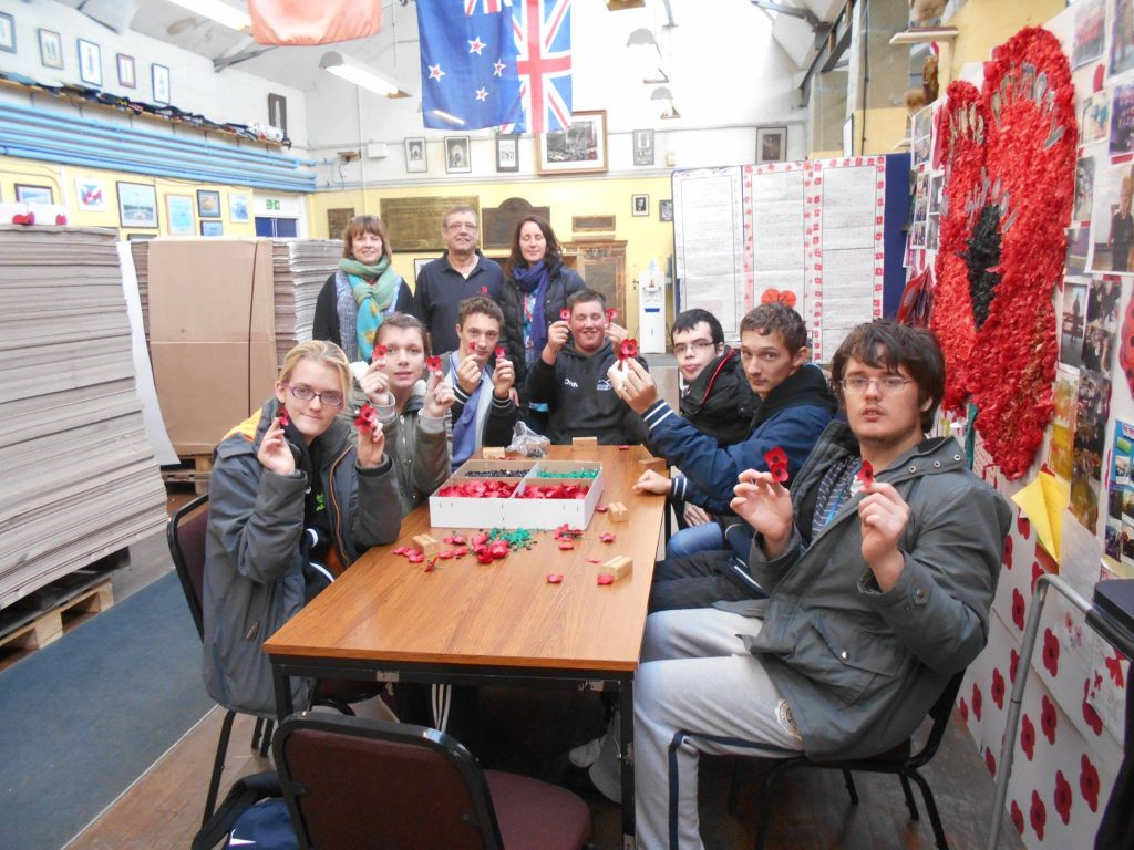 College students making poppies during their visit to the Poppy Factory