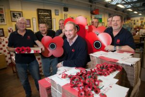 Manager of the Poppy Factory alongside some of the disabled veterans